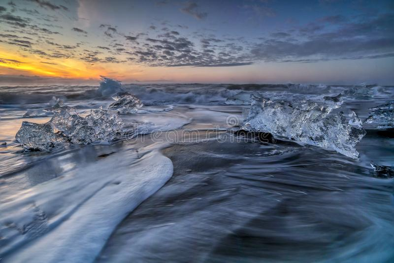 Ondas que rabian que rompen bloques de hielo en la salida del sol en Diamond Beach fotografía de archivo libre de regalías