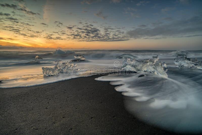 Ondas que rabian que rompen bloques de hielo en la salida del sol en Diamond Beach fotos de archivo