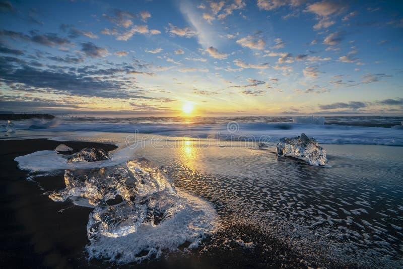 Ondas que rabian que rompen bloques de hielo en la salida del sol en Diamond Beach fotos de archivo libres de regalías