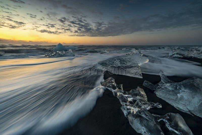 Ondas que rabian que rompen bloques de hielo en la salida del sol en Diamond Beach imagen de archivo libre de regalías