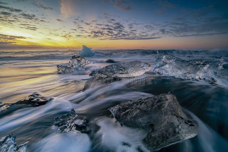 Ondas que rabian que rompen bloques de hielo en la salida del sol en Diamond Beach imágenes de archivo libres de regalías
