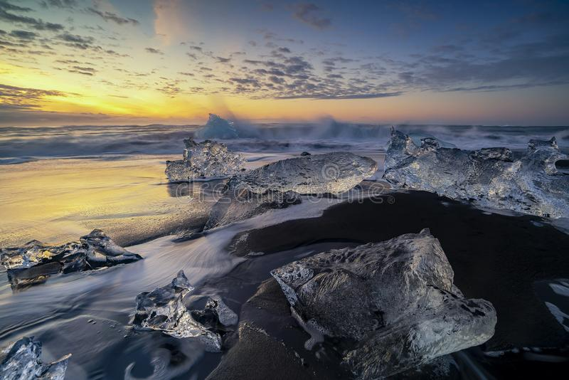 Ondas que rabian que rompen bloques de hielo en la salida del sol en Diamond Beach imagenes de archivo