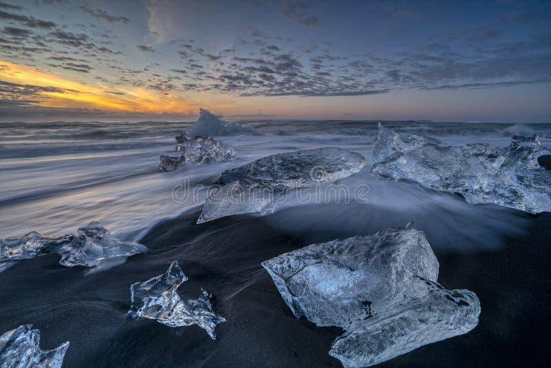 Ondas que rabian que rompen bloques de hielo en la salida del sol en Diamond Beach foto de archivo libre de regalías