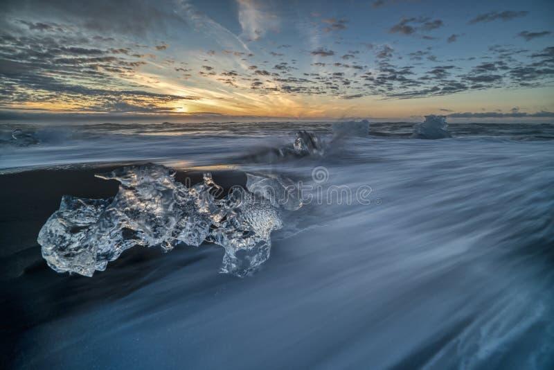 Ondas que rabian que rompen bloques de hielo en la salida del sol en Diamond Beach fotografía de archivo