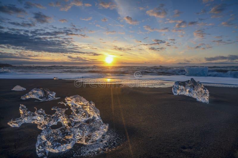 Ondas que rabian que rompen bloques de hielo en la salida del sol en Diamond Beach imagen de archivo