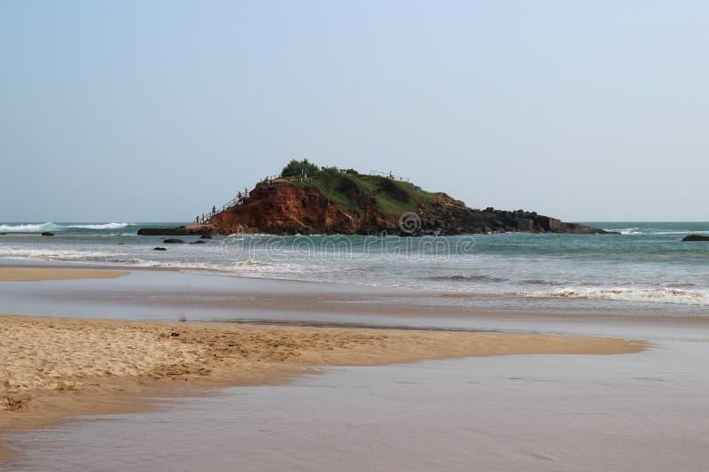 Ondas que se rompen en la colina en el medio de la playa arenosa fotografía de archivo