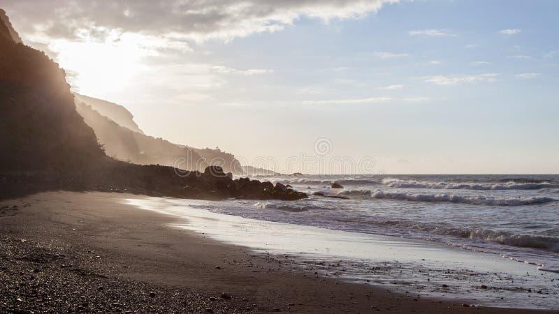 Ondas que se rompen en la orilla de una playa de Tenerife con la luz trasera de la puesta del sol inminente imagen de archivo