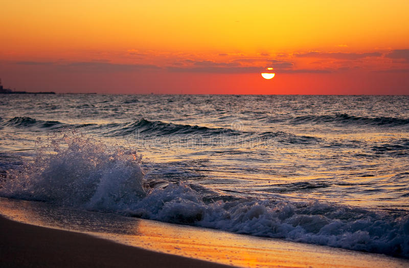 Ondas que se rompen en la puesta del sol fotografía de archivo