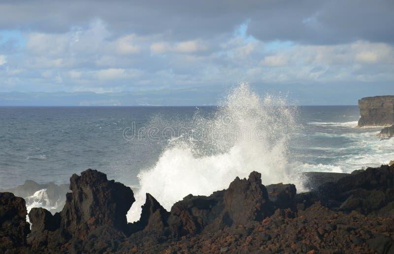 Ondas que se rompen en los acantilados de la lava imagenes de archivo