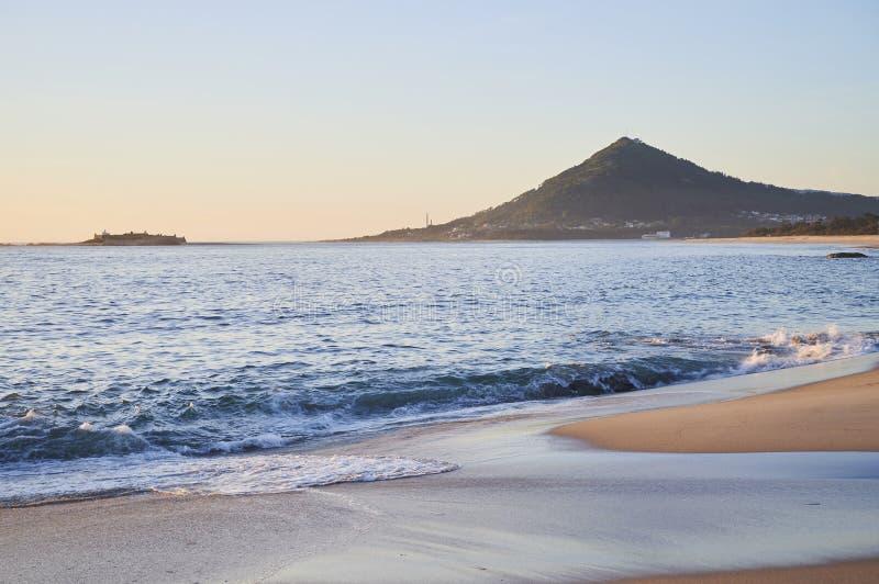 Ondas sobre una playa arenosa con la montaña en fondo fotografía de archivo libre de regalías