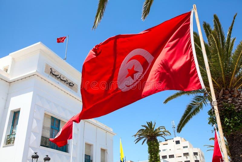 Ondas tunecinas rojas de la bandera nacional contra el edificio administrativo en la ciudad de Sousse Todos los edificios del gob imagenes de archivo