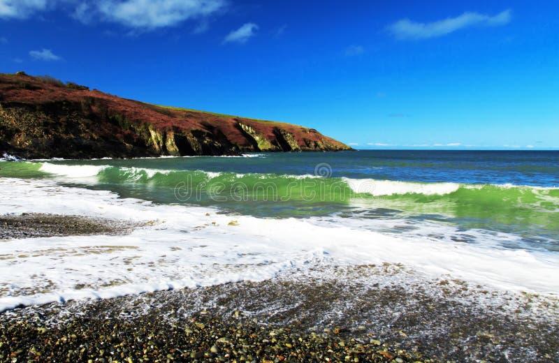 Ondas verdes esmeraldas que deixam de funcionar em um Pebble Beach imagem de stock