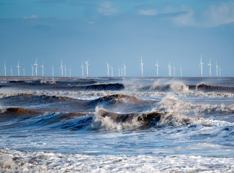 Ondas Windblown que quebram na costa com uma exploração agrícola de vento no horizonte imagem de stock