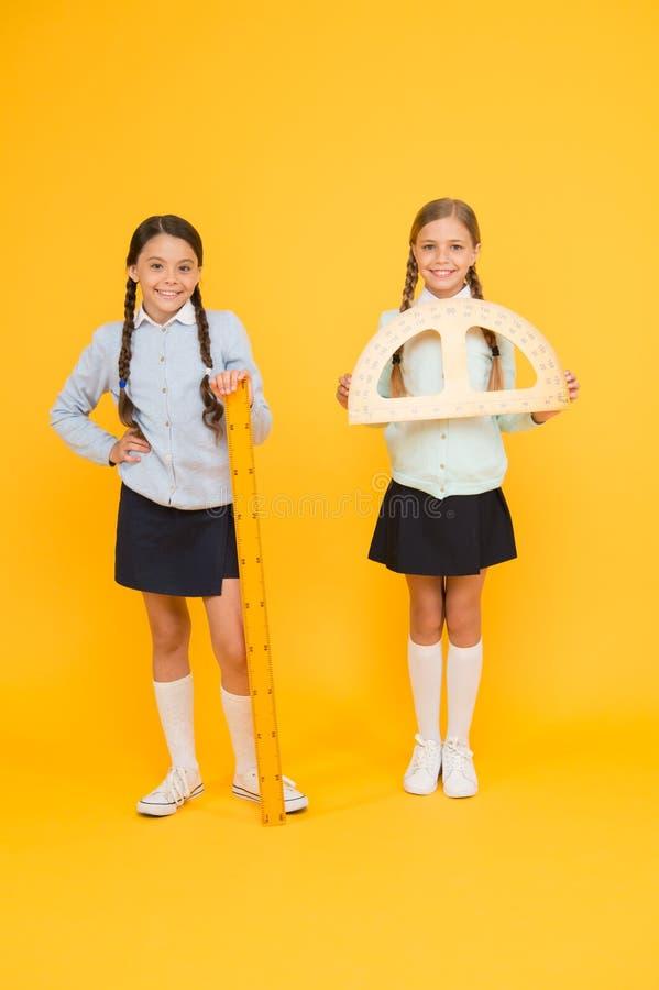 Onde alunos que conseguem a excelência junto Alunos bonitos que guardam o prolongador e régua no fundo amarelo Pupilas pequenas imagens de stock