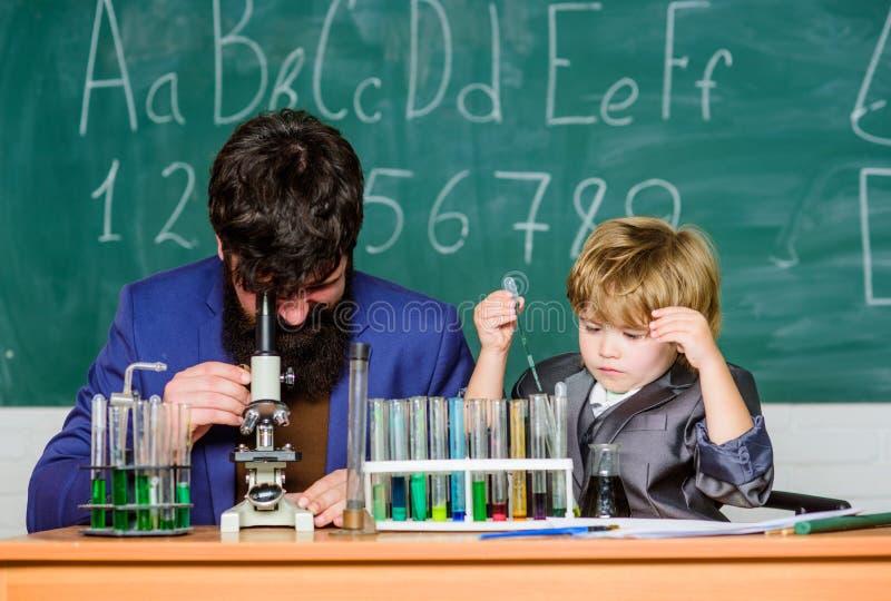 Onde aprender começa pai e filho na escola professor farpado do homem com rapaz pequeno Carisma da confian?a De volta a imagens de stock