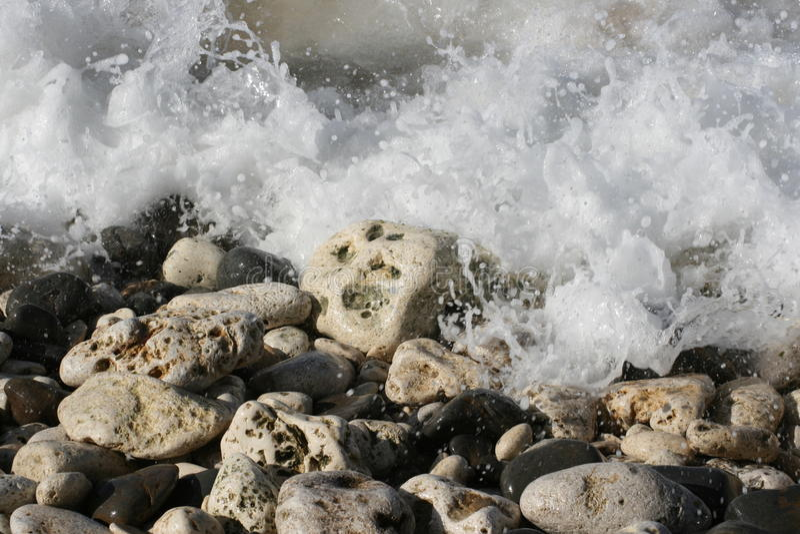 Onde che si arrestano sulle rocce ad una spiaggia fotografia stock