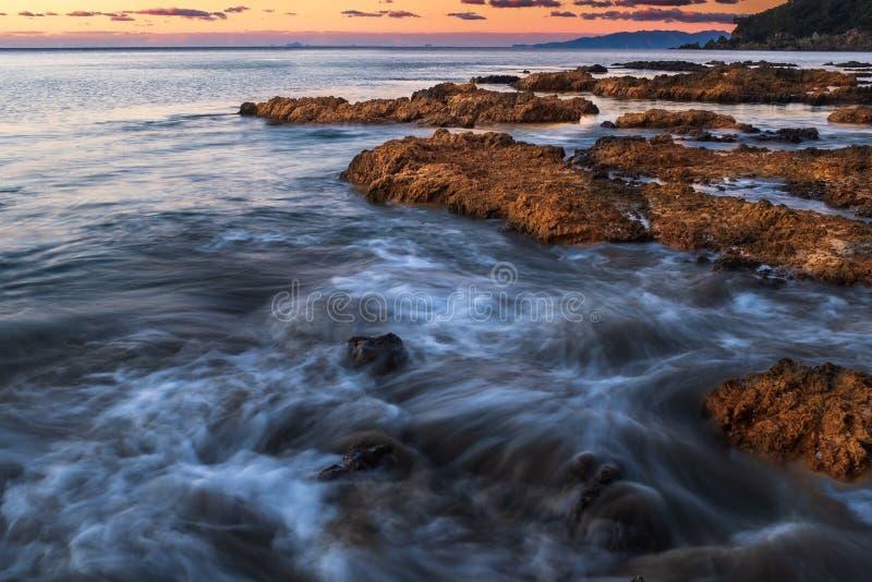 Onde che si schiantano sopra le rocce sulla linea costiera dentellata dell'isola di Waiheke, Nuova Zelanda presa su un'esposizion fotografia stock