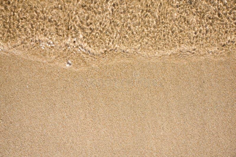 Onde de l'eau sur la plage de sable photo libre de droits