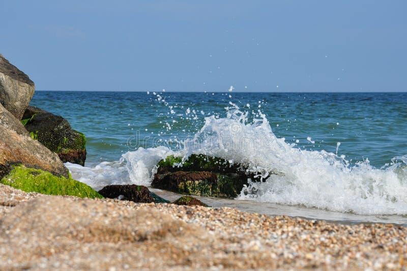 Onde del mare che si rompono sulle rocce Puntello di mare spumoso fotografia stock