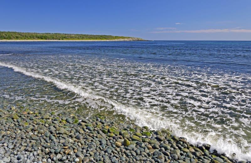 Onde di oceano su una spiaggia arrotondata della roccia fotografia stock