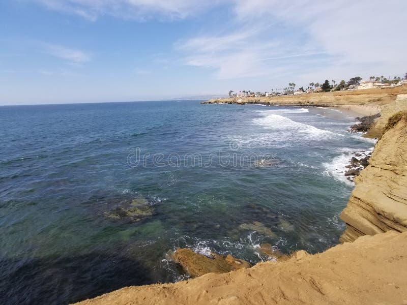 Onde di oceano sulla spiaggia con le scogliere della roccia immagini stock libere da diritti