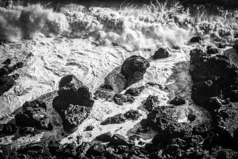 Onde drammatiche che si schiantano sulla riva rocciosa fotografia stock