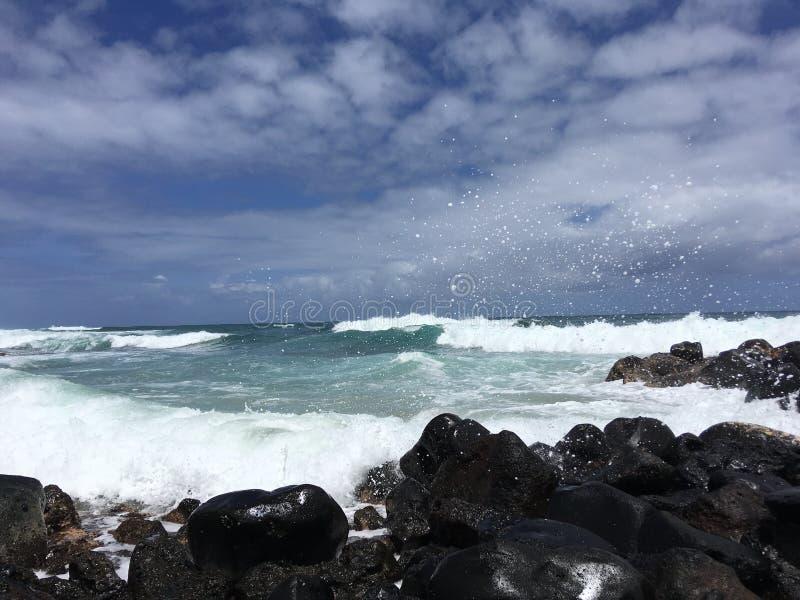 Onde e Lava Rocks di oceano Pacifico alla spiaggia di Kealia sull'isola di Kauai in Hawai fotografia stock