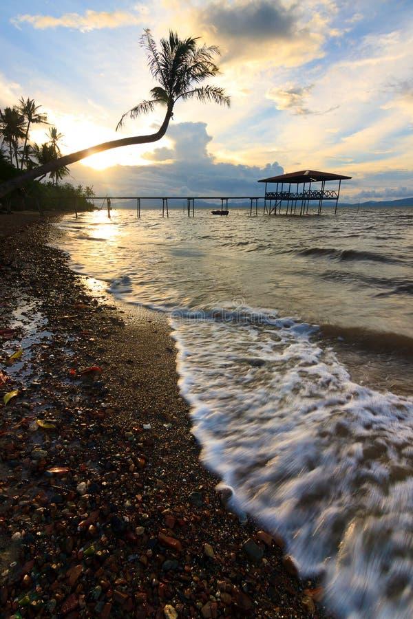 Onde e tramonto ad una spiaggia immagini stock libere da diritti