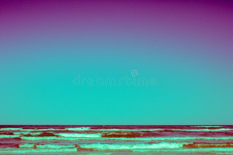 Onde magenta che colpiscono spiaggia su estate immagini stock