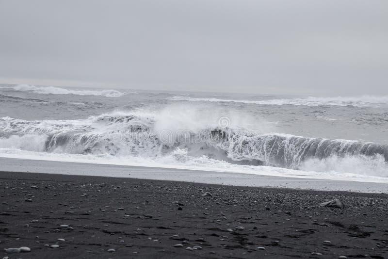 Onde nella bella spiaggia di sabbia nera vulcanica fotografia stock libera da diritti