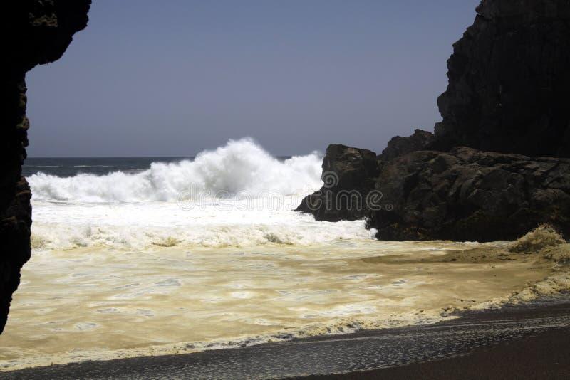 Onde potenti che si schiantano su una roccia e che spruzzano acqua nell'aria sulla spiaggia di sabbia nera a distanza della lava  fotografia stock libera da diritti