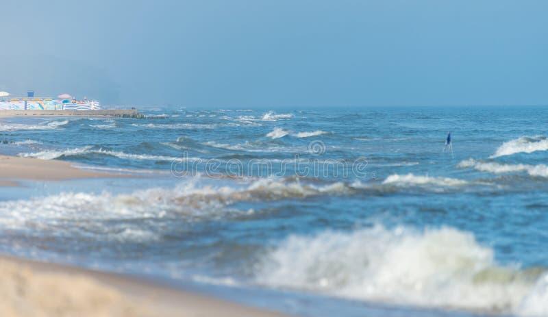 Onde ruvide su un bello mare blu un giorno soleggiato e ventoso di estate, Bandiere d'avvertimento di sporgenza dal mare fotografia stock