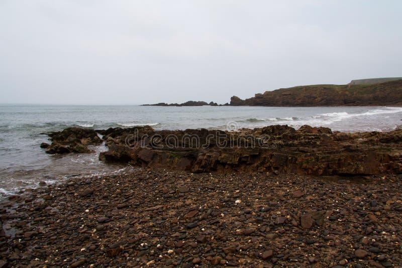 Onde sopra le rocce sulla spiaggia fotografia stock libera da diritti