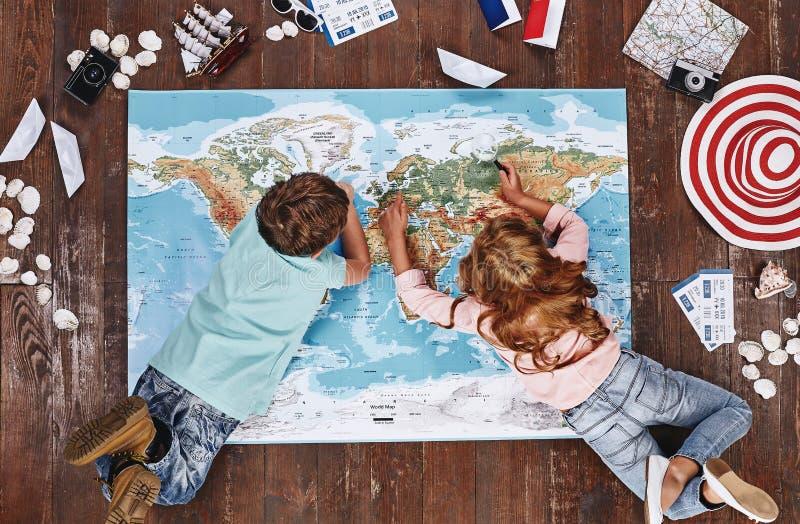 Onde você gostaria de visitar as crianças que olham o mapa do mundo, ao se encontrar nele, perto dos artigos do curso imagem de stock