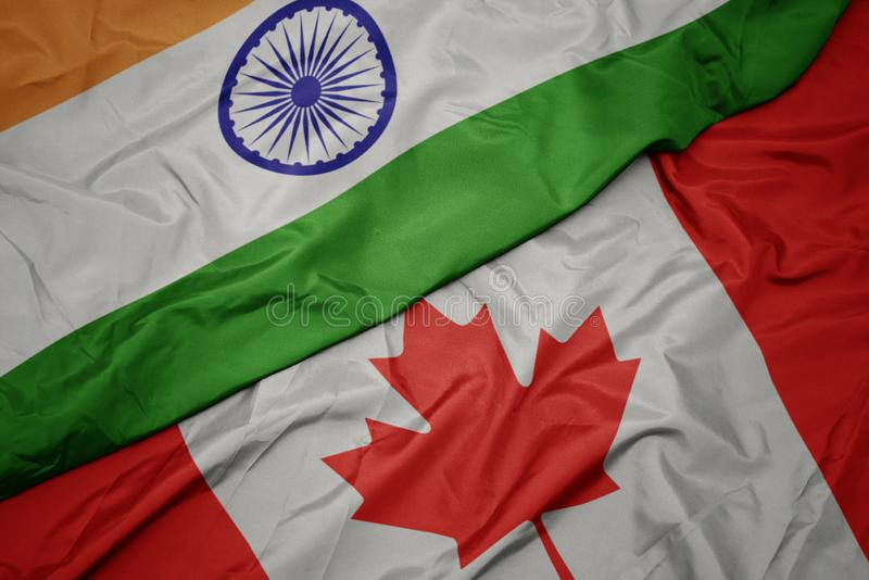 ondeando la colorida bandera de Canadá y la bandera nacional de India imágenes de archivo libres de regalías