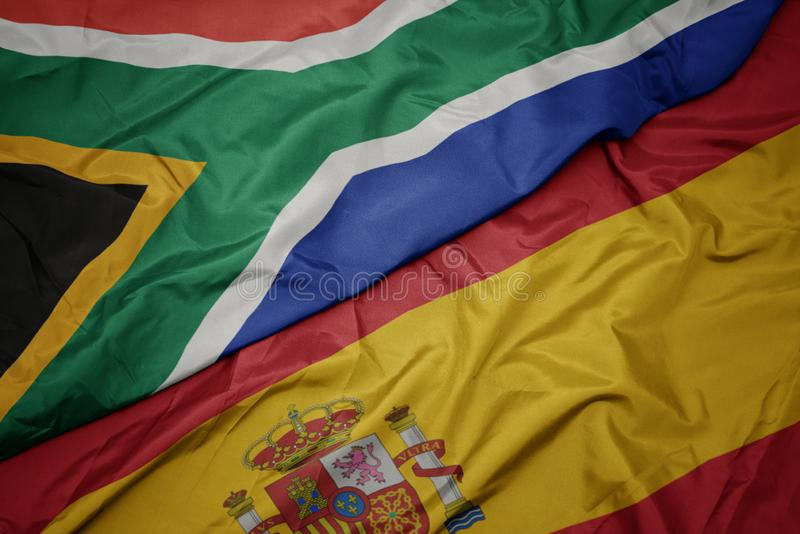 ondeando la colorida bandera de España y la bandera nacional de Sudáfrica fotos de archivo