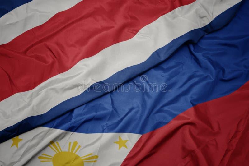 ondeando la colorida bandera de Filipinas y la bandera nacional de Costa Rica fotos de archivo