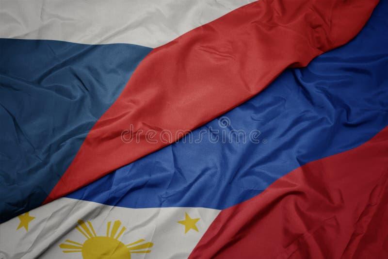 ondeando la colorida bandera de Filipinas y la bandera nacional de la república checa foto de archivo