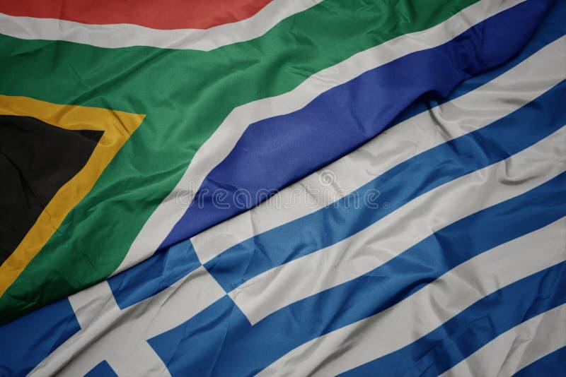 ondeando la colorida bandera de Grecia y la bandera nacional de Sudáfrica foto de archivo