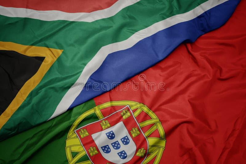 ondeando la colorida bandera portugal y la bandera nacional de Sudáfrica foto de archivo libre de regalías