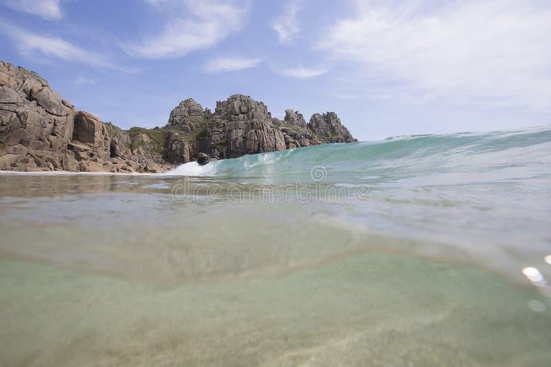 Ondeggi la rottura alla spiaggia di Porthcurno, davanti a Logan Rock fotografia stock libera da diritti
