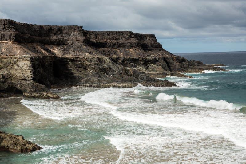 Ondeggi la spruzzatura sopra una roccia sulla spiaggia di Puertito il de il los Molinos su Fuerteventura fotografia stock