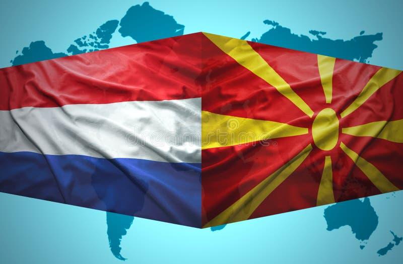 Ondeggiamento delle bandiere macedoni e olandesi royalty illustrazione gratis