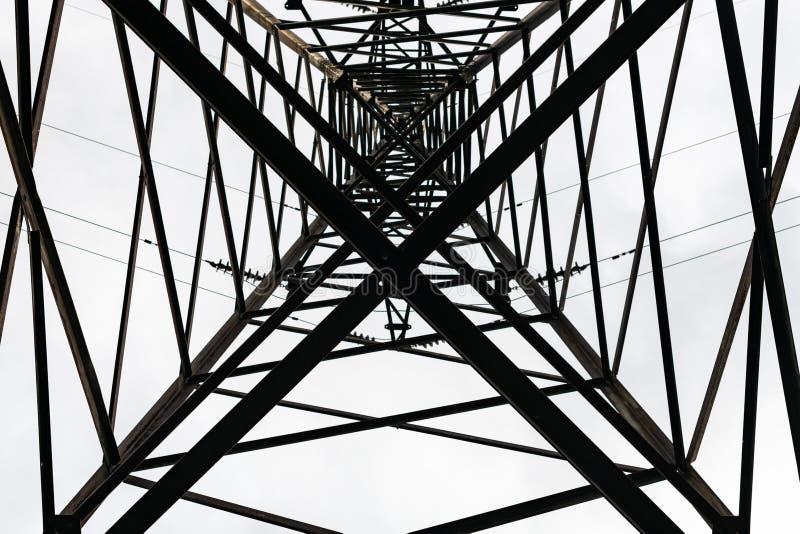 Onder de luchttoren met hoog voltage van de machtslijn Mening van bodem van bouw stock afbeeldingen