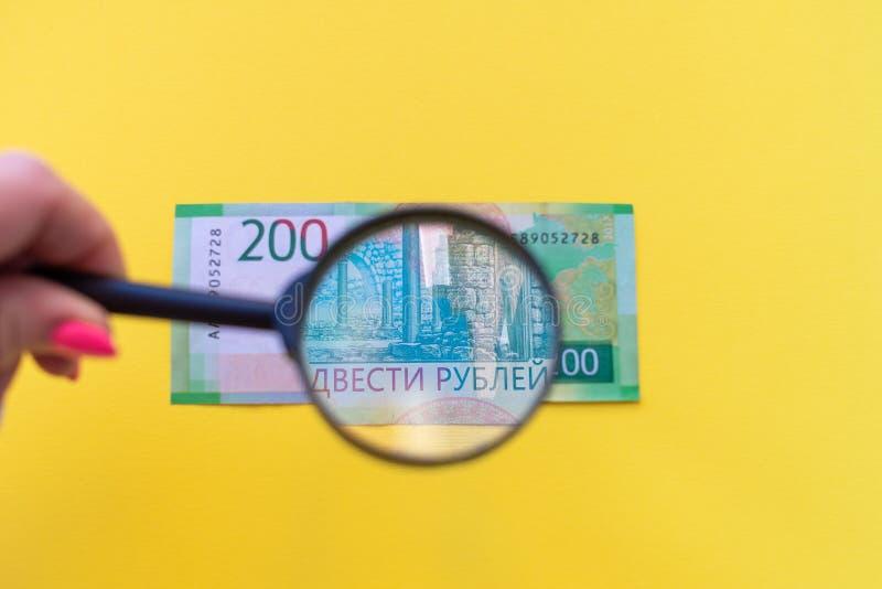 Onder een vergrootglas die een 200 roebelbankbiljet bekijken voor authenticiteit stock foto