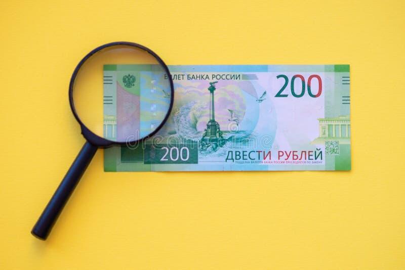 Onder een vergrootglas die een 200 roebelbankbiljet bekijken voor authenticiteit stock afbeeldingen