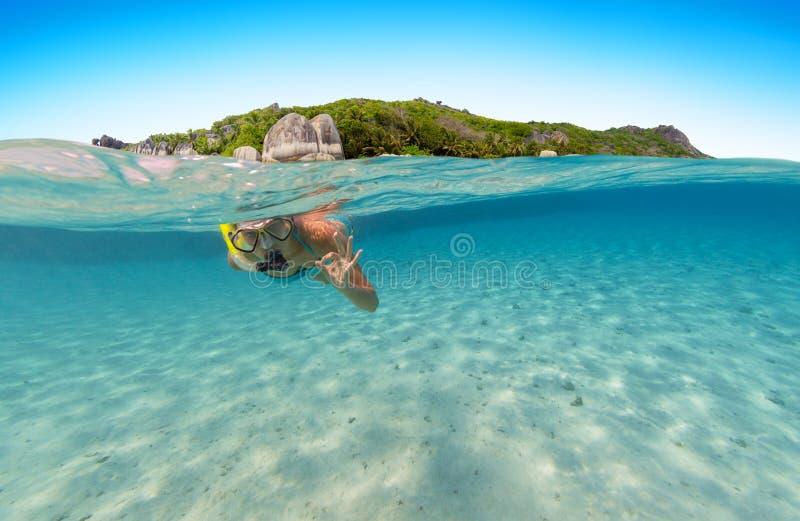 Onder en hierboven - watermening van vrouw het snorkelen royalty-vrije stock afbeeldingen