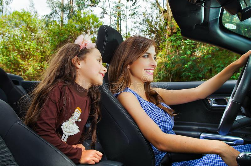 Onder mening van mooie jonge vrouw met haar daugher binnen van de zwarte auto, die haar auto met één hand, in a drijven royalty-vrije stock afbeeldingen