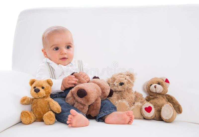 Onder speelgoed: leuke babyzitting op witte bank met teddyberen stock foto's