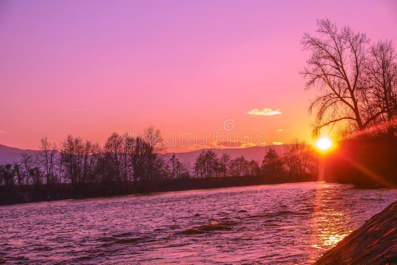 Onderaan door de rivier, gaat de zonsondergang over door stock afbeeldingen